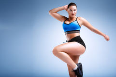 Plus size female model in a studio. Plus size female model is posing in a fitness style in a studio Royalty Free Stock Photography