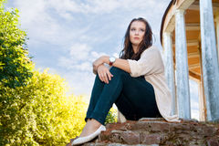 Plus size girl sits on an old brick wall Stock Images
