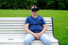 Plus size man wearing virtual reality goggles outdoors Stock Image