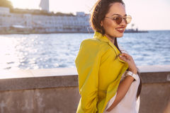Plus size model in bright fall outfit. Young stylish woman wearing bright colorful blazer and sunglasses walking on the city street. Casual fashion, fall look Royalty Free Stock Photo