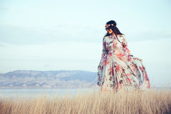 Plus size model in floral dress. Plus size model wearing floral maxi dress posing in field. Young and fashionable overweight woman walking on the shore Stock Image