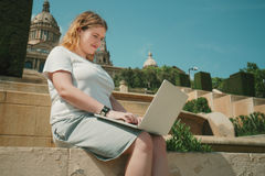 Plus size model girl working on laptop outdoors Stock Image