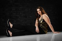 Plus size model in a gold blouse and black jeans on a brick loft background. Beautiful young brunette girl with long hair. Sexy, self-confident. Sits on white Stock Photos