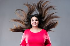 Plus size model with long hair blowing in the wind, brunette fat woman on gray background, body positive concept. Plus size model with long hair blowing in the stock image