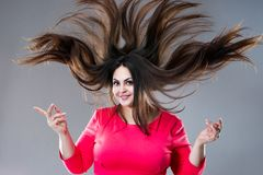 Plus size model with long hair blowing in the wind, brunette fat woman on gray background, body positive concept. Plus size model with long hair blowing in the royalty free stock photo