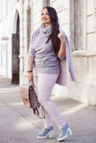 Plus size model in pink coat. Young stylish woman wearing pink warm coat, pants and handbag walking in the city street in cold season. Winter fashion, elegant Stock Photos