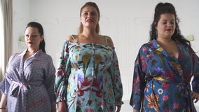 Plus size models in a beautiful dresses in the studio. Smiling plump women posing in beautiful outfits.