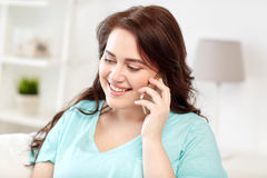 Plus size woman calling on smartphone at home Stock Photos