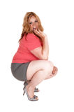 Plus size woman crouching in shorts and heels. Royalty Free Stock Photo