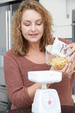 Plus Size Woman On Diet Weighing Out Pasta For Meal Royalty Free Stock Image