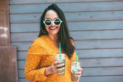 Plus size woman drinking take away cocktail over city cafe wall. Plus size woman wearing yellow shirt and white hipster glasses smiling and drinking take away royalty free stock images