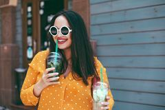 Plus size woman drinking take away cocktail over city cafe wall. Plus size woman wearing yellow shirt and white hipster glasses smiling and drinking take away stock photo