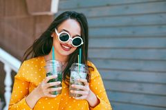 Plus size woman drinking take away cocktail over city cafe wall. Plus size woman wearing yellow shirt and white hipster glasses smiling and drinking take away royalty free stock photography