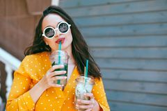 Plus size woman drinking take away cocktail over city cafe wall. Plus size woman wearing yellow shirt and white hipster glasses smiling and drinking take away royalty free stock photo