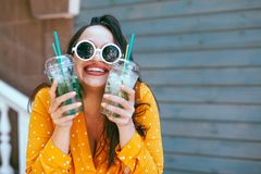 Plus size woman drinking take away cocktail over city cafe wall. Plus size woman wearing yellow shirt and white hipster glasses smiling and drinking take away stock photography