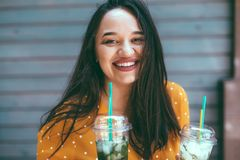 Plus size woman drinking take away cocktail over city cafe wall. Plus size woman wearing yellow shirt smiling and drinking take away vegetable cocktail with ice stock photos