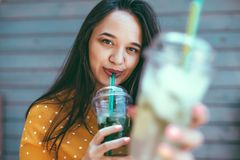 Plus size woman drinking take away cocktail over city cafe wall. Plus size woman wearing yellow shirt smiling and drinking take away vegetable cocktail with ice royalty free stock photo