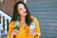 Plus size woman drinking take away cocktail over city cafe wall. Plus size woman wearing yellow shirt smiling and drinking take away vegetable cocktail with ice royalty free stock photography