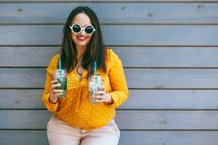 Plus size woman drinking take away cocktail over city cafe wall. Plus size woman wearing yellow shirt and white hipster glasses smiling and drinking take away royalty free stock photos