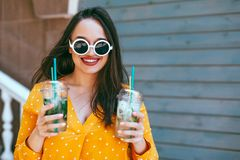 Plus size woman drinking take away cocktail over city cafe wall. Plus size woman wearing yellow shirt and white hipster glasses smiling and drinking take away stock images