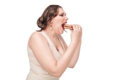 Plus size woman eating hamburger. Beautiful plus size woman eating hamburger isolated Royalty Free Stock Photos