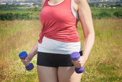 Plus size woman exercising with dumbbells Stock Photos