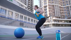 Plus size woman exercising with dumbbells outdoors. Side view of overweight female doing sports exercise holding dumbbells during fitness workout on city stadium stock footage