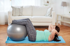 Plus size woman exercising with fitness ball Stock Images