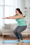 Plus size woman exercising on mat at home Royalty Free Stock Images
