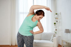 Plus size woman exercising and stretching at home Royalty Free Stock Photography