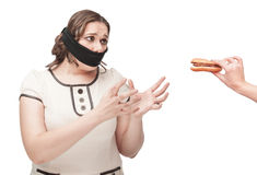 Plus size woman gagged stretching hands to hamburger. Beautiful brunette plus size woman gagged stretching hands to hamburger isolated stock photos