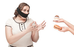 Plus size woman gagged stretching hands to junk food. Beautiful brunette plus size woman gagged stretching hands to junk food isolated royalty free stock photo