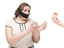 Plus size woman gagged stretching hands to pastry. Beautiful brunette plus size woman gagged stretching hands to pastry isolated stock images