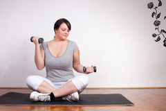 Plus size woman lifting weights at home Royalty Free Stock Images