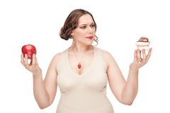 Plus size woman making choice between apple and pastry Royalty Free Stock Photos