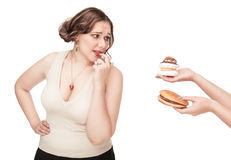 Plus size woman seduced with hamburger and pastry Royalty Free Stock Image