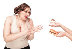 Plus size woman seduced with hamburger and pastry Stock Photo