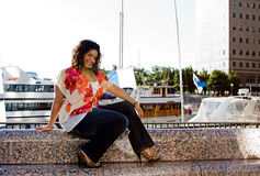 Plus size woman sitting. Beautiful plus size woman sitting at a marina catching a breeze stock photo
