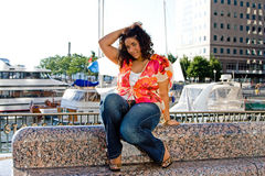 Plus size woman sitting. Beautiful plus size woman sitting at a marina catching a breeze and holding hair stock photo
