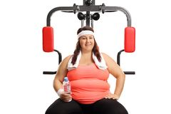 Plus size woman sitting on a multifunctional gym machine with a bottle of water stock photos