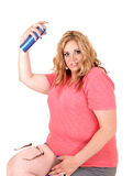 Plus size woman straying hairspray on. Royalty Free Stock Images