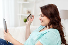 Plus size woman with tablet pc and credit card Stock Image