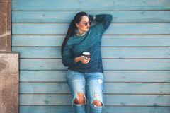 Plus size woman walking on the city street. Beautiful woman wearing fall sweater, ripped jeans and glasses drinking take away coffee standing against cafe wall Stock Photo