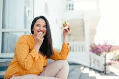 Plus size woman walking down the city and eating burger royalty free stock photography