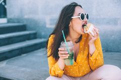Plus size woman walking down the city and eating burger stock image