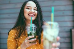 Plus size woman drinking take away cocktail over city cafe wall. Plus size woman wearing yellow shirt smiling and drinking take away vegetable cocktail with ice royalty free stock images