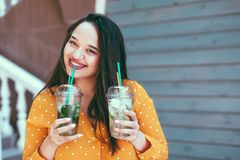 Plus size woman drinking take away cocktail over city cafe wall. Plus size woman wearing yellow shirt smiling and drinking take away vegetable cocktail with ice royalty free stock photos