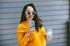 Plus size woman drinking take away cocktail over city cafe wall. Plus size woman wearing yellow shirt and white hipster glasses smiling and drinking take away stock image