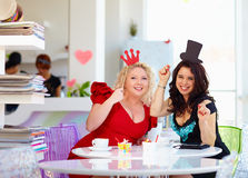 Plus size women friends enjoying life, having fun in cafe Royalty Free Stock Image