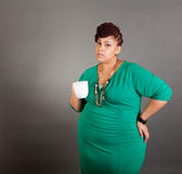 Plus sized business woman. Plus sized african american business woman wearing a green dress holding a white ceramic coffee or tea cup on a grey background Royalty Free Stock Images
